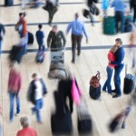 Couple embraced in a busy airport while people are in motion blu